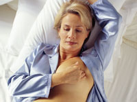 woman-bed-breast-self-exam