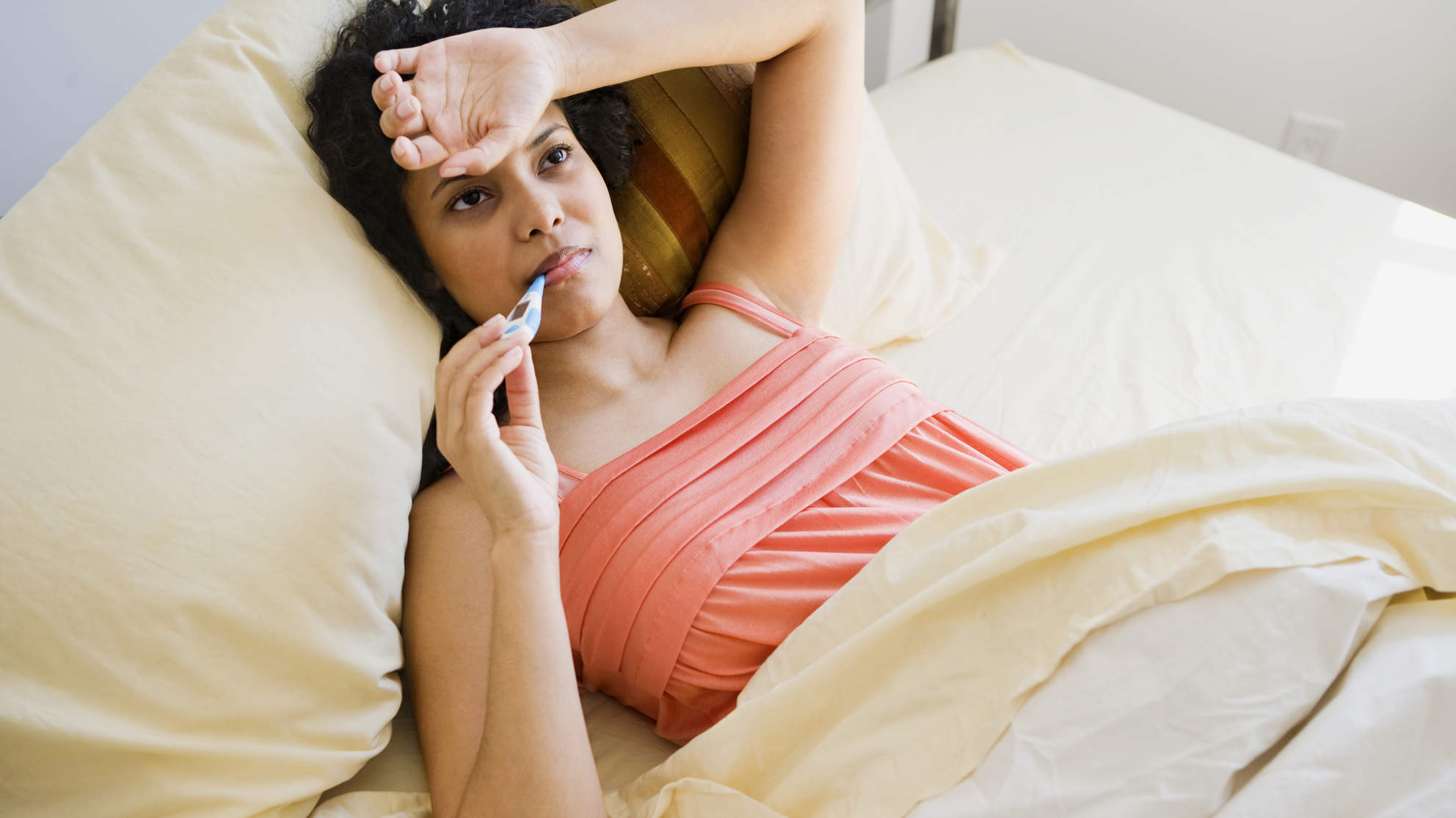 Woman taking temperature with fever and flu in bed