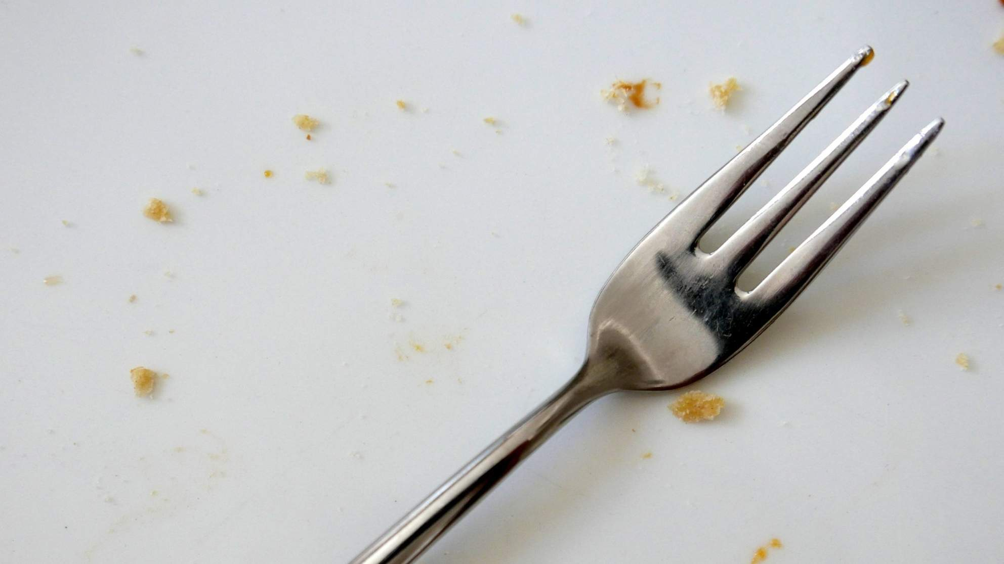 Close-Up Of Fork With Scattered Food Against White Background