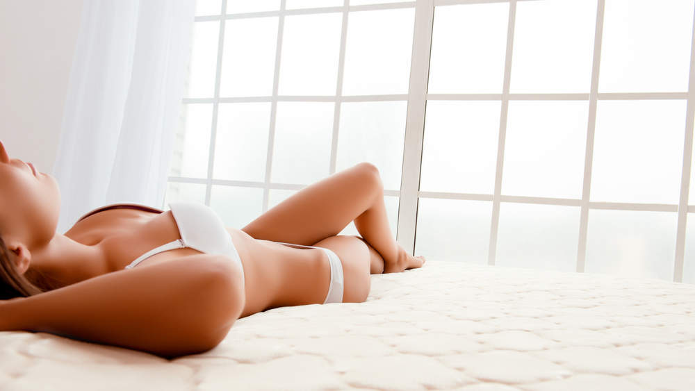 Woman lies on a white mattress in white undergarments