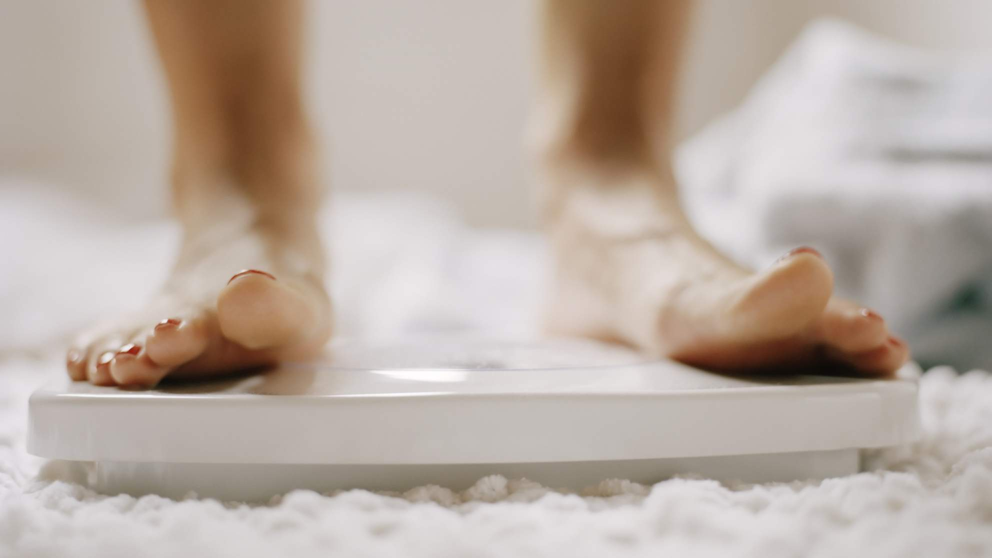 Close-up of woman's feet on scale TIME health stock