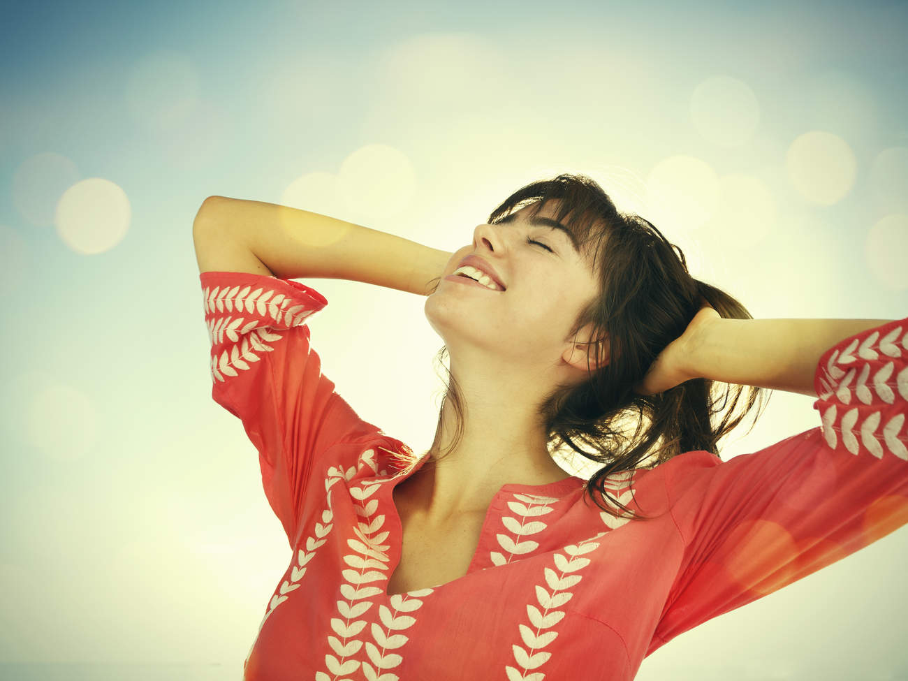 Woman smiling looking at a blue sky