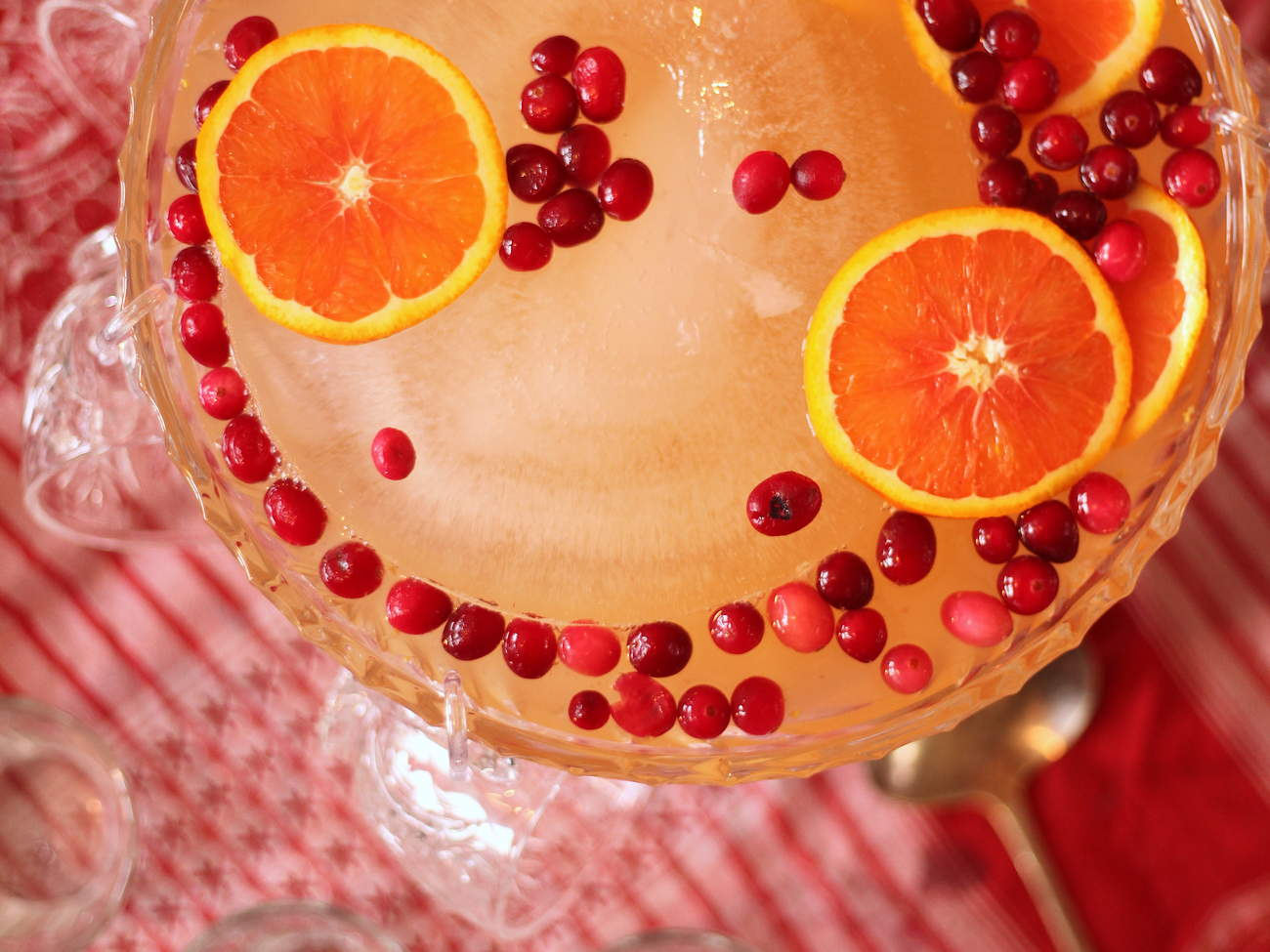 Party punch in a bowl garnished with cranberries and orange slices on a table