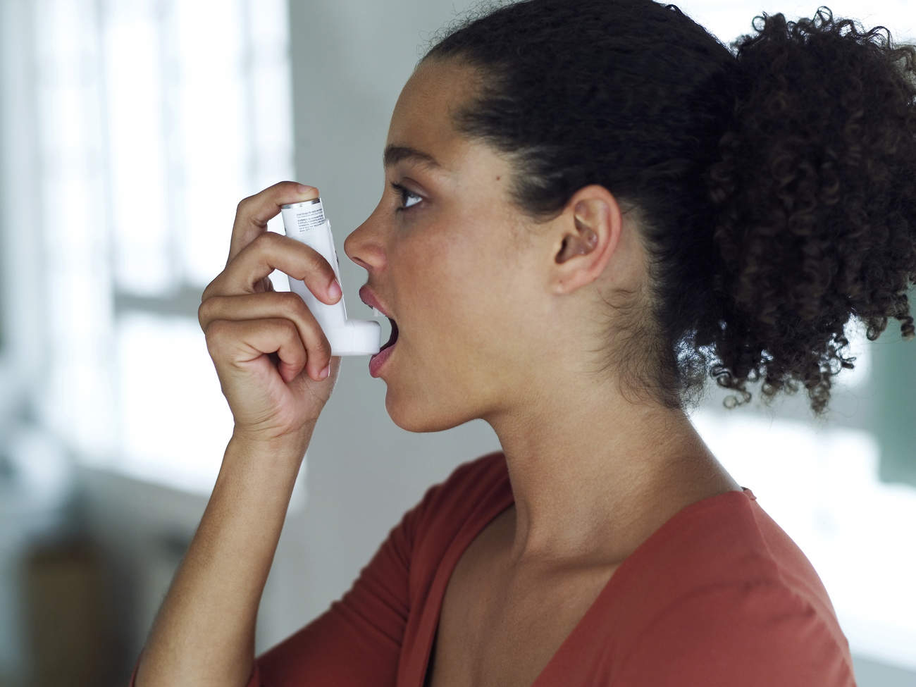 Woman using asthma inhaler