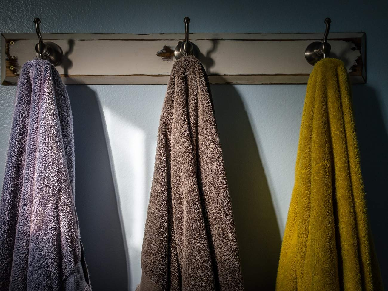 Towels Hanging On Hook Against Wall In Bathroom
