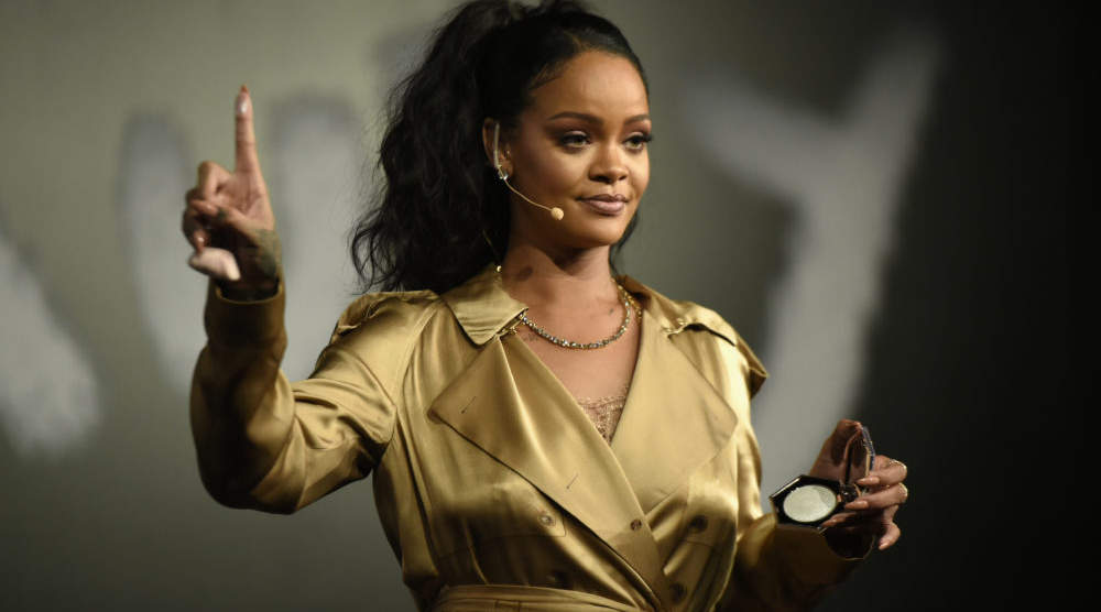 DUBAI, UNITED ARAB EMIRATES - SEPTEMBER 29: Rihanna gestures on stage during her Fenty Beauty talk in collaboration with Sephora, for the launch of her new Stunna Lip paint  Uninvited  on September 29, 2018 in Dubai, United Arab Emirates.