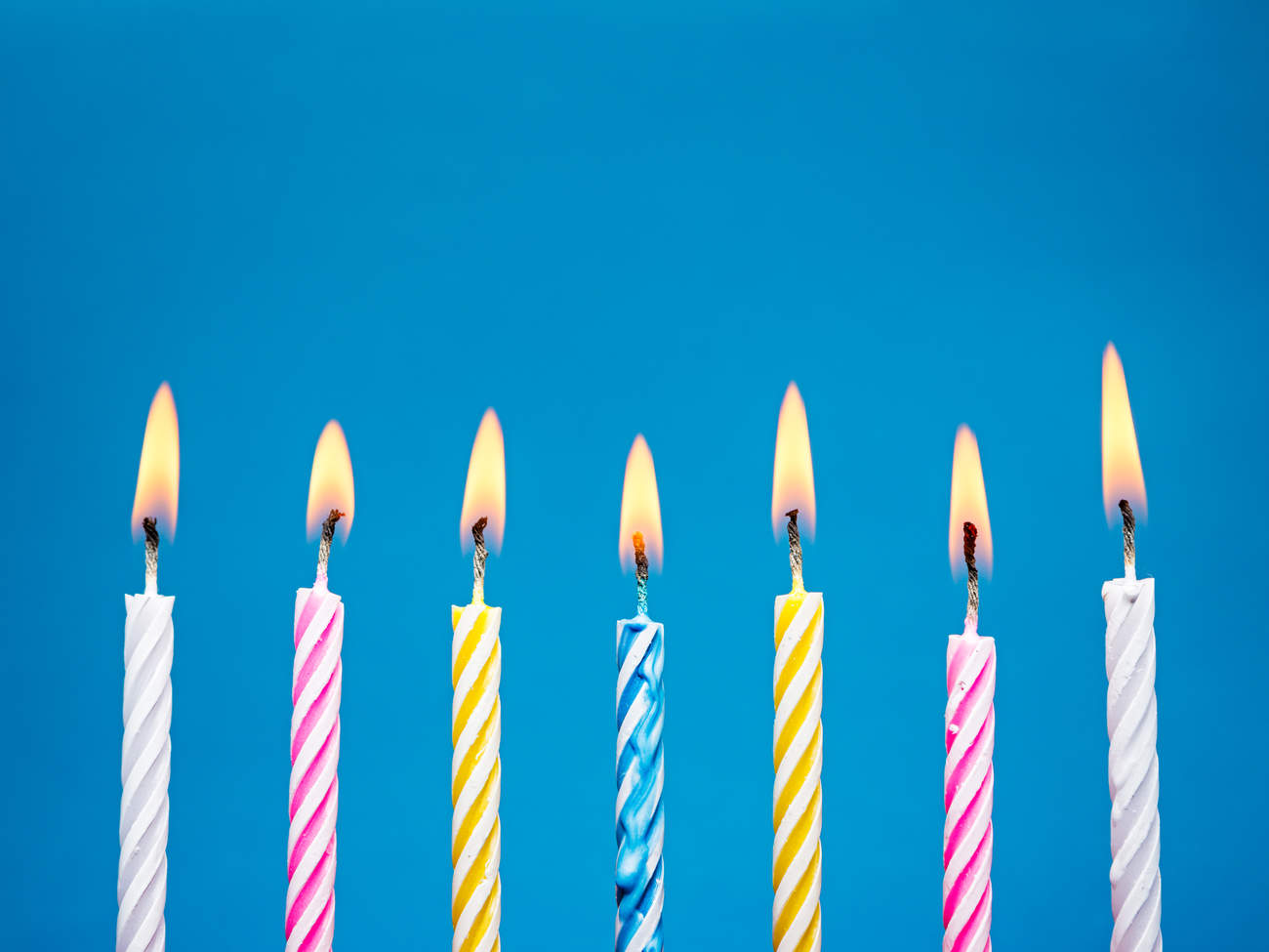 Flaming Birthday Candles on blue background TIME health stock