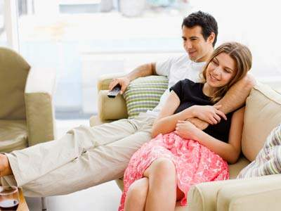 couple on couch looking happy