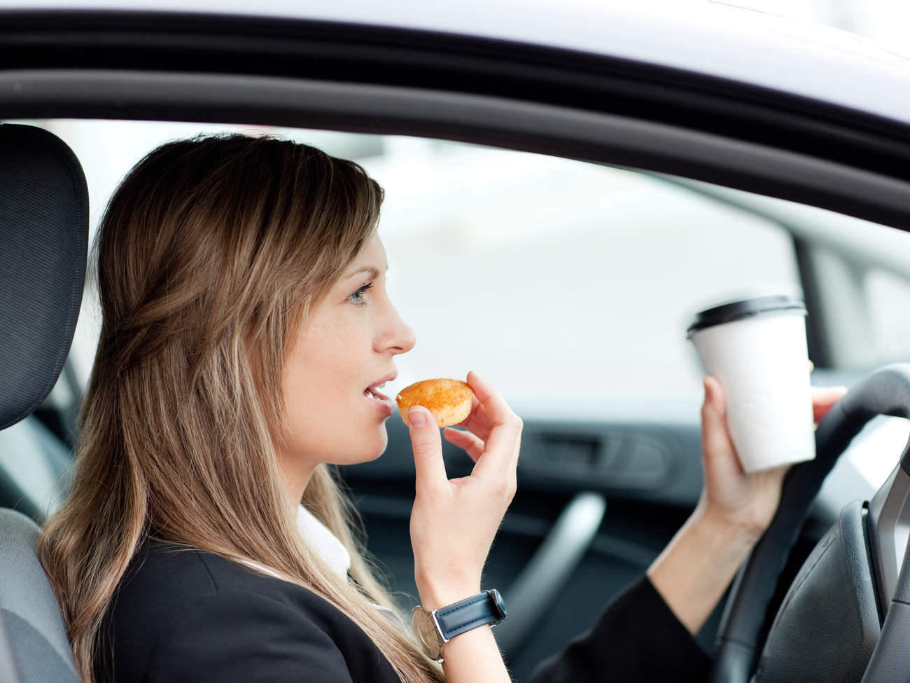 Woman eating and drinking while driving to work