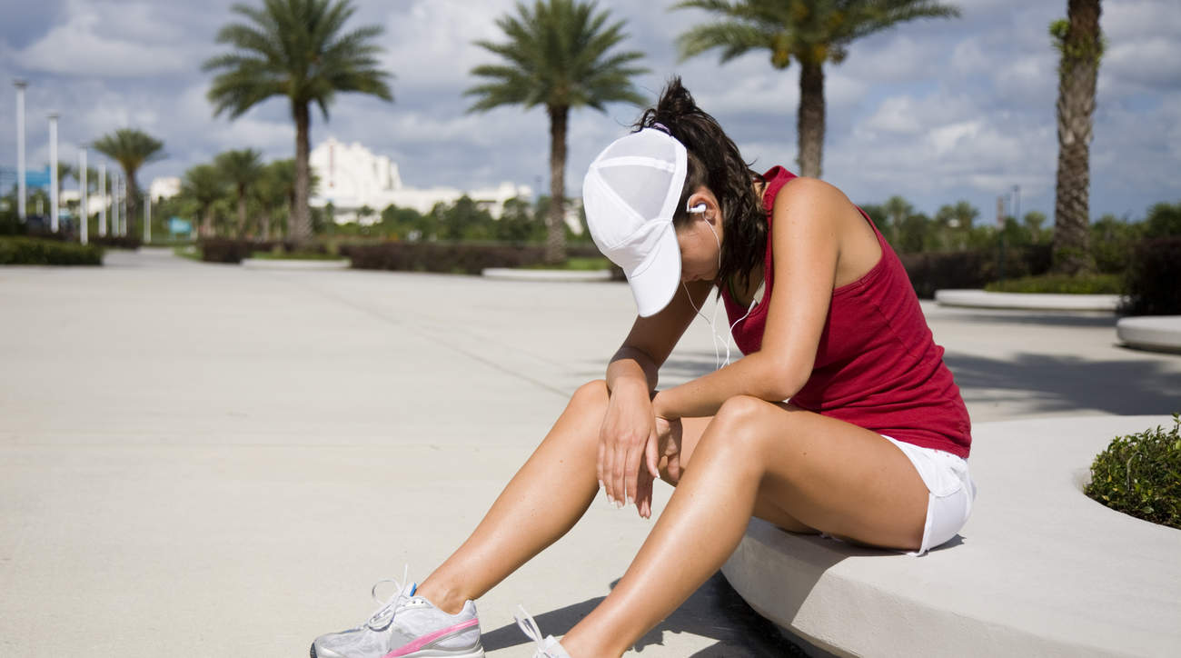 Woman sitting down after workout feeling nauseous