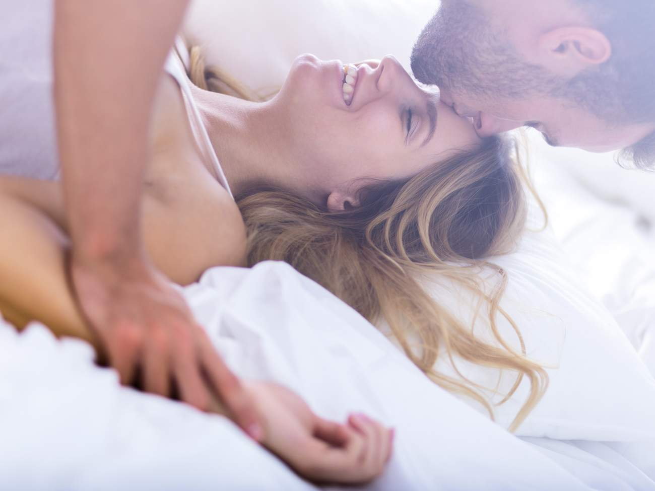 man and woman in bed smiling and having fun