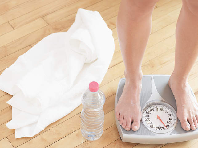 Woman standing on weight scale water weight bloating swelling