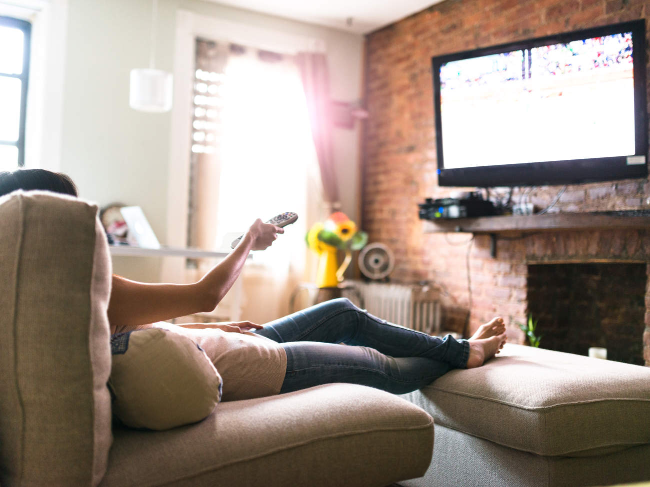 Woman lounging on couch watching TV