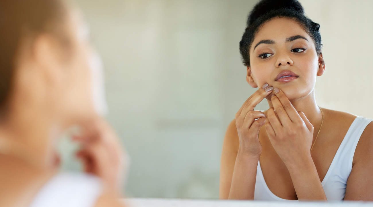 Woman popping pimple acne in mirror