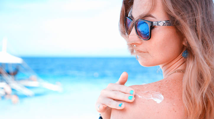 young woman with sunglasses applying sun protector cream on the beach