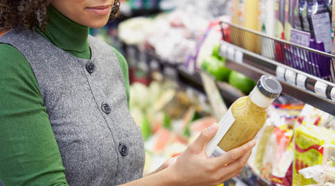 Woman reading salad dressing label at grocery store