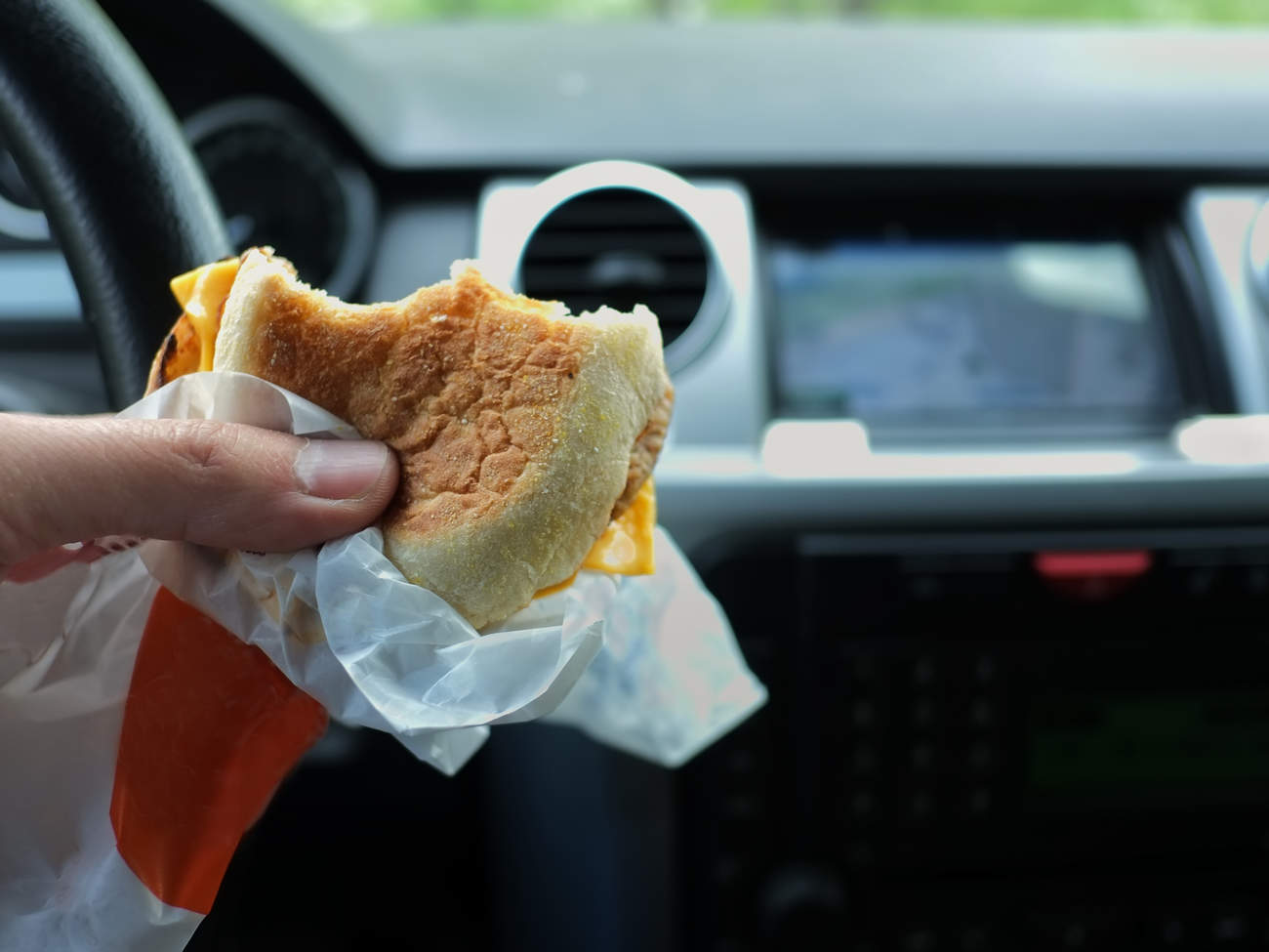 Driver eating fast food burger in car