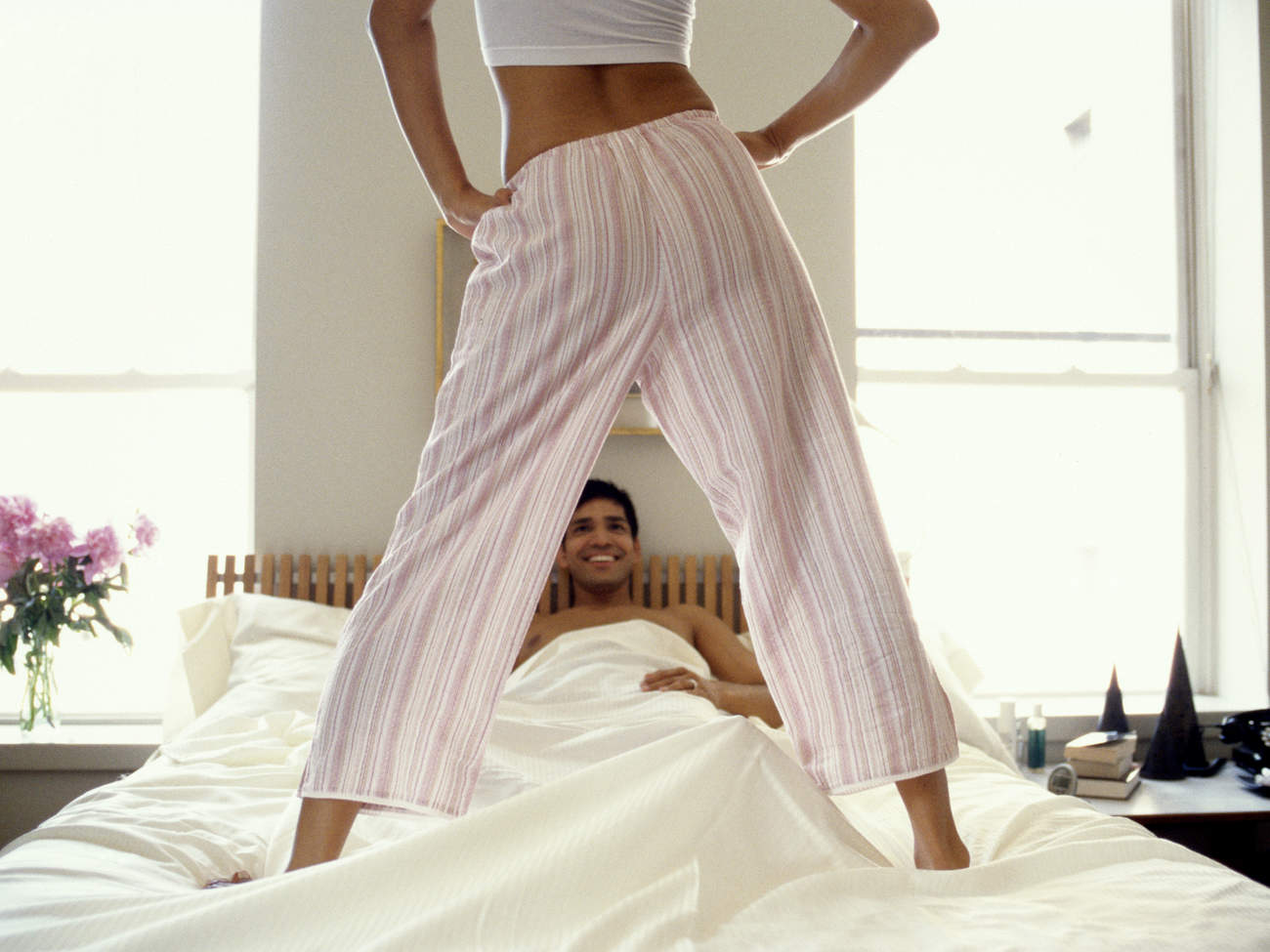Woman standing over a man in bed