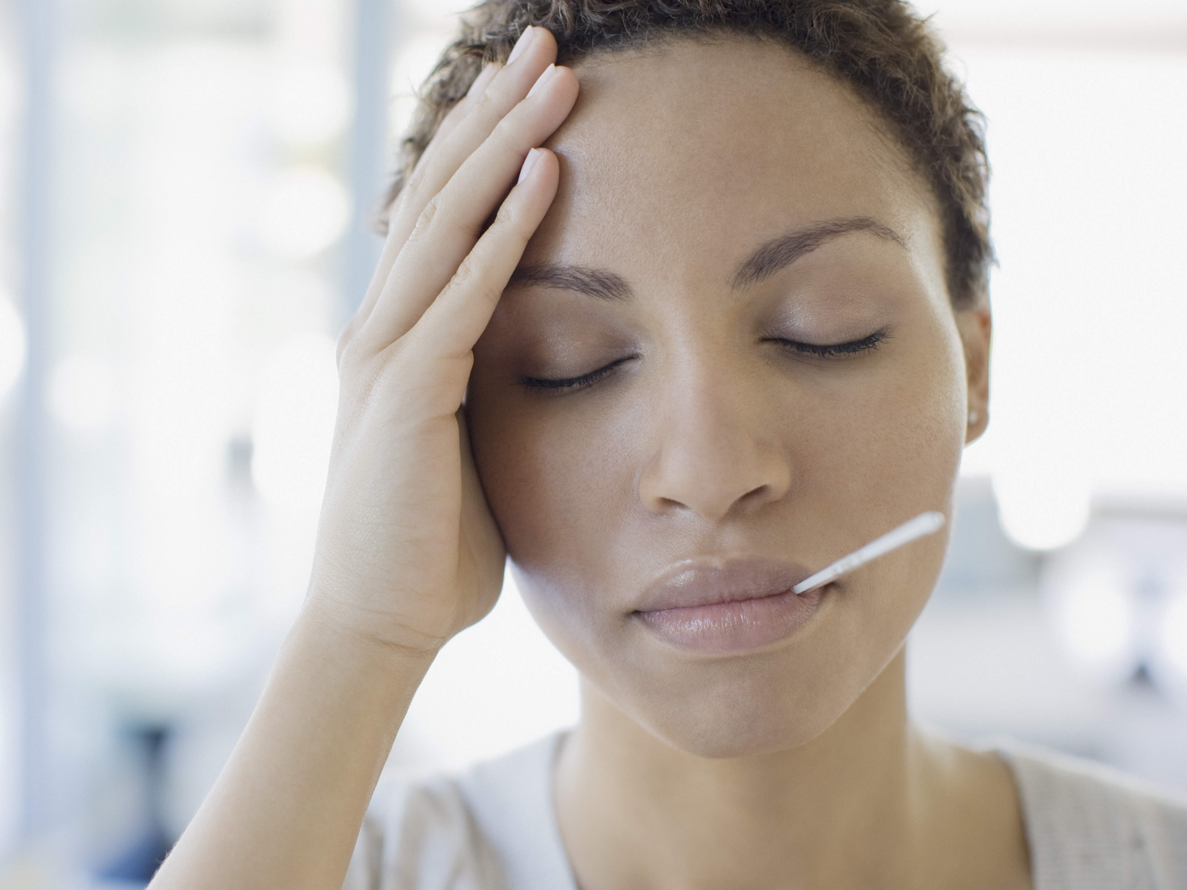 woman feeling sick with thermometer in mouth