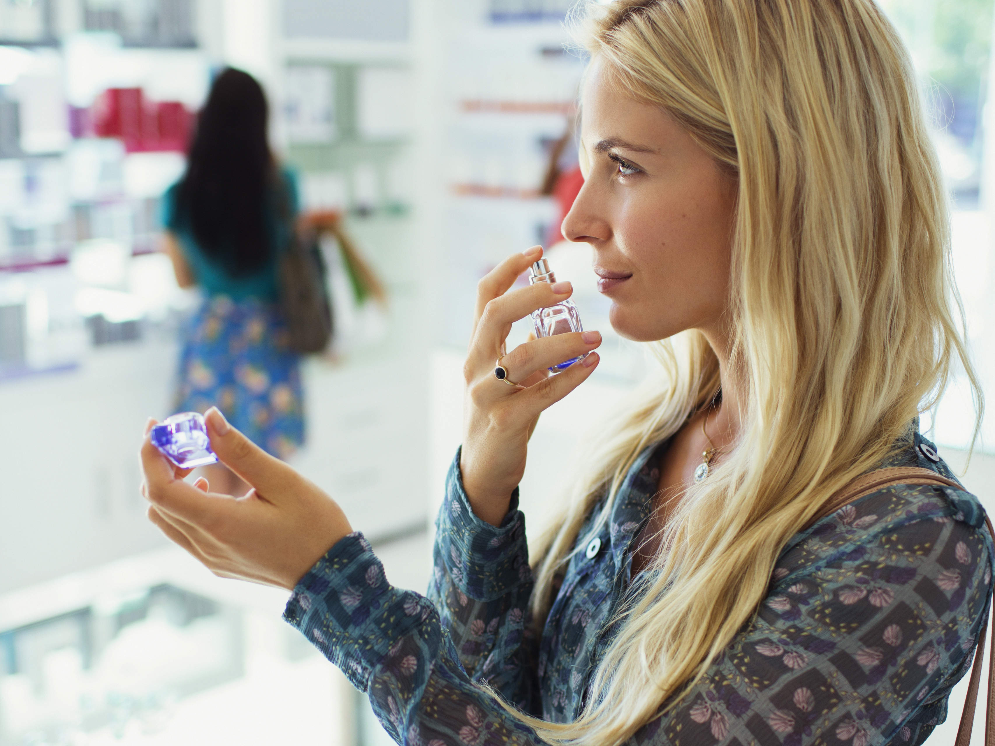 Woman smelling perfume at fragrance counter