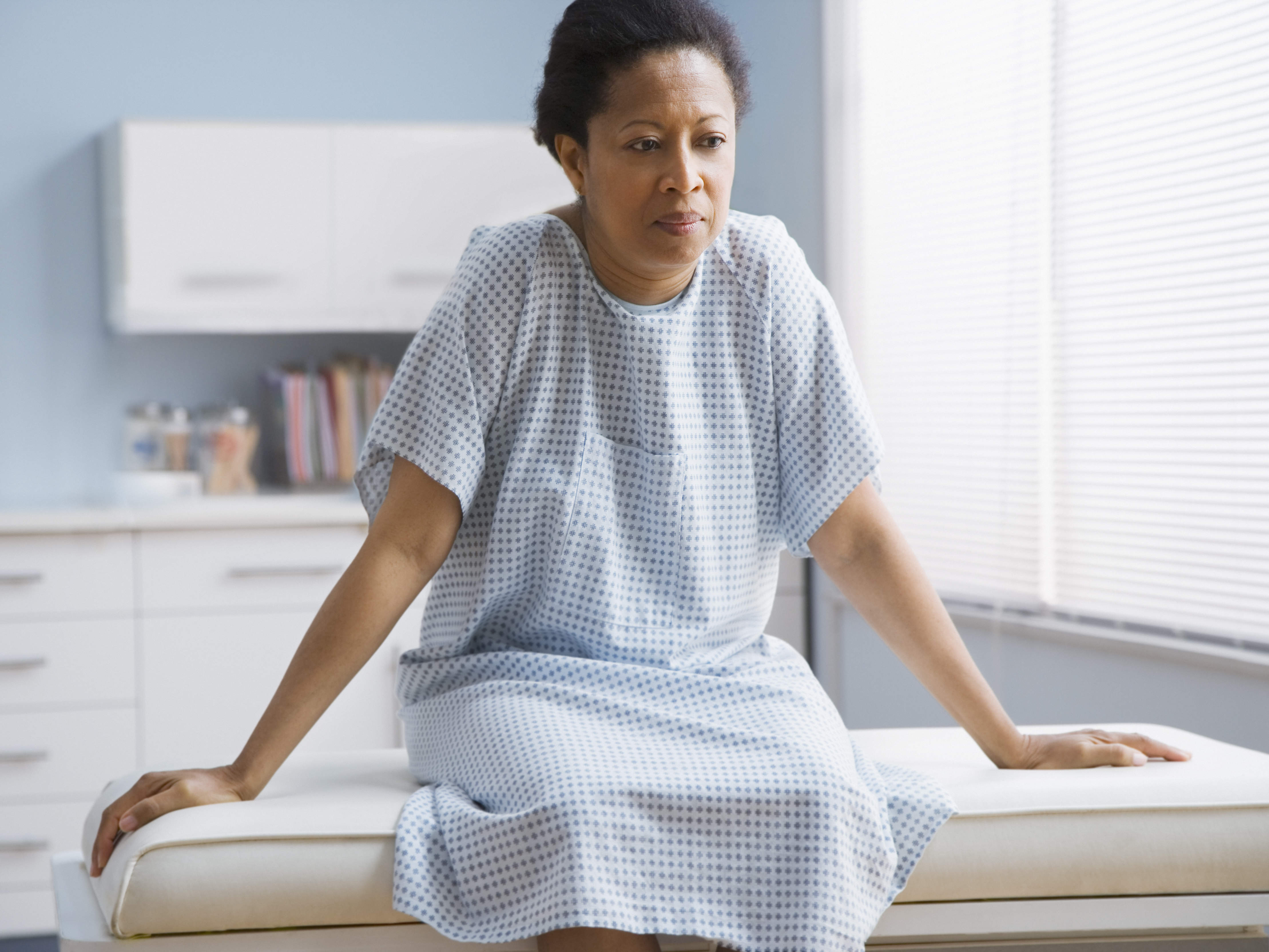 woman in medical gown on doctor exam table