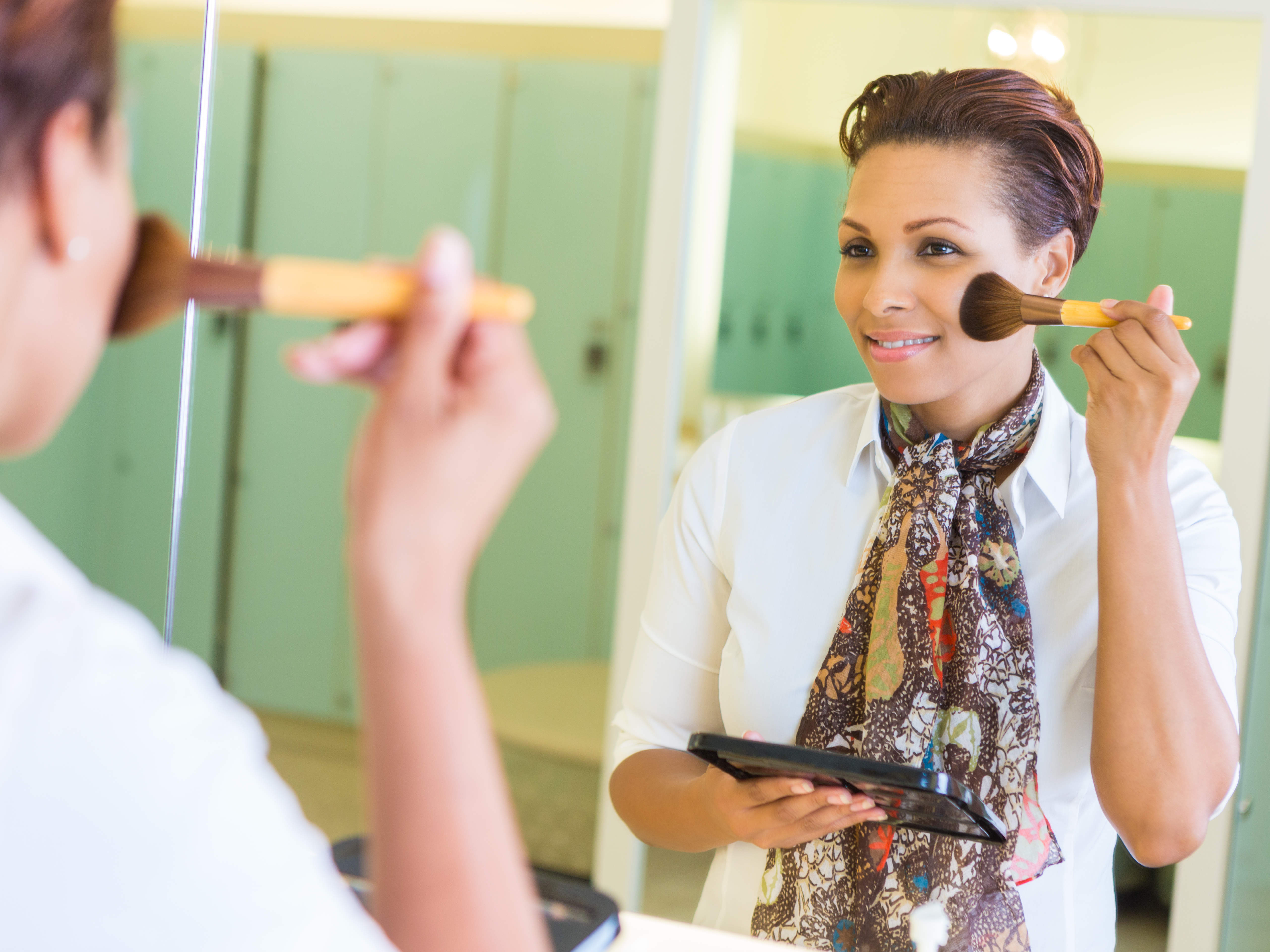 Woman applying makeup in front of a mirror in a gym locker room