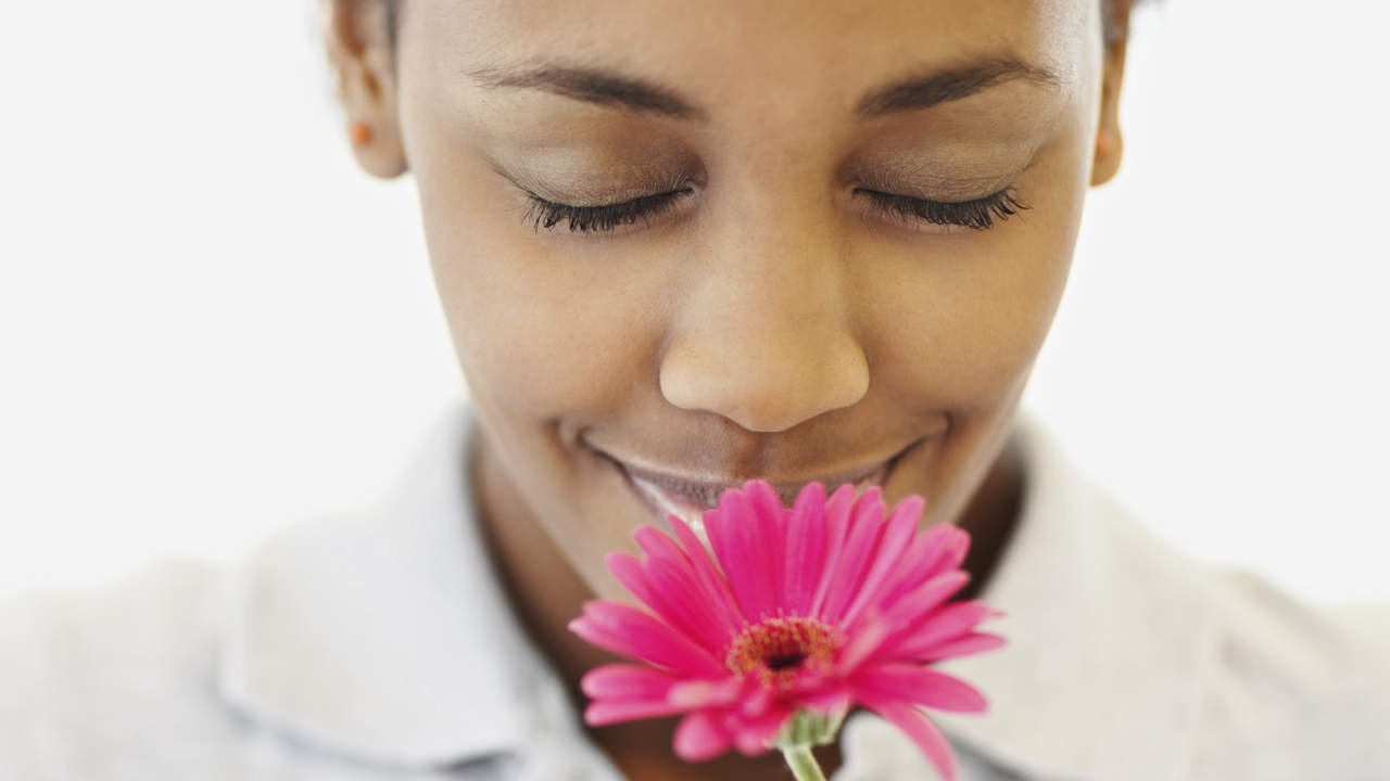 Woman smelling a flower with allergies