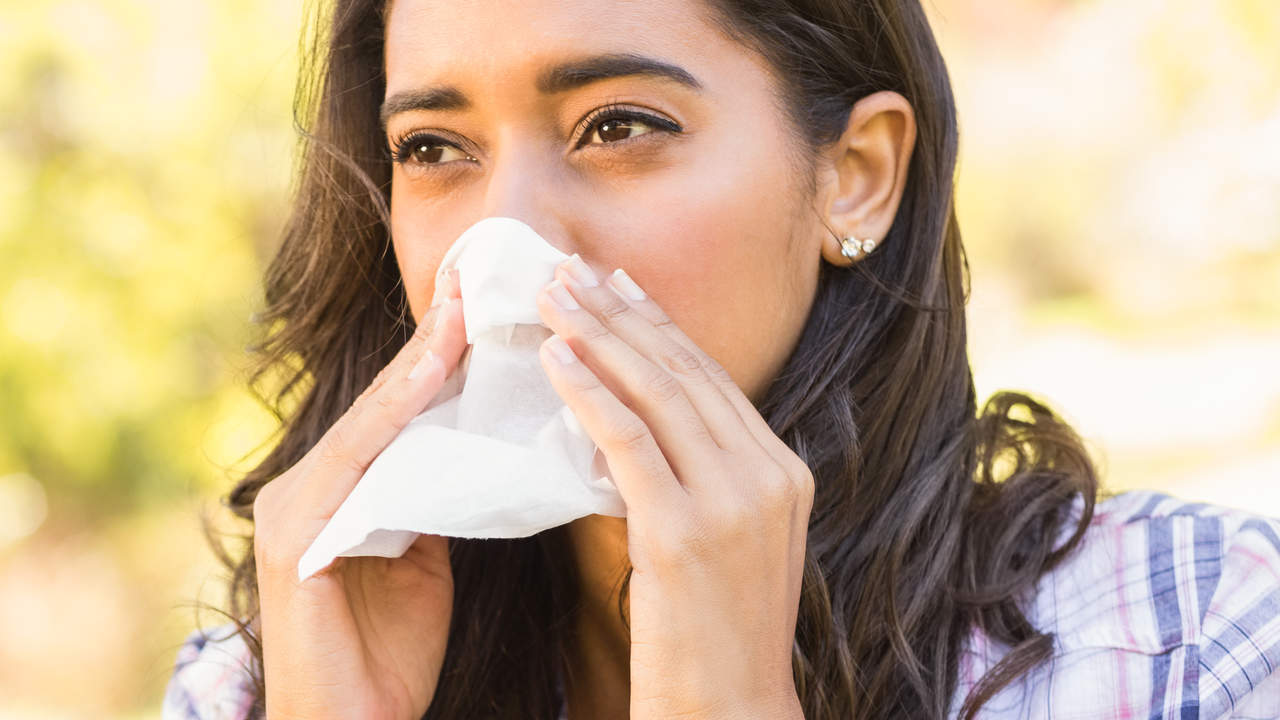 Woman blowing runny congested nose spring allergies cold symptoms pink eye antihistamines