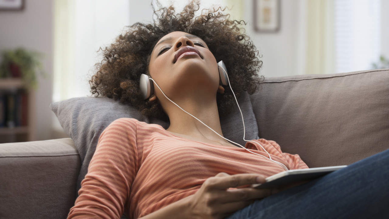 Woman listening to music with headphones on a couch relaxing
