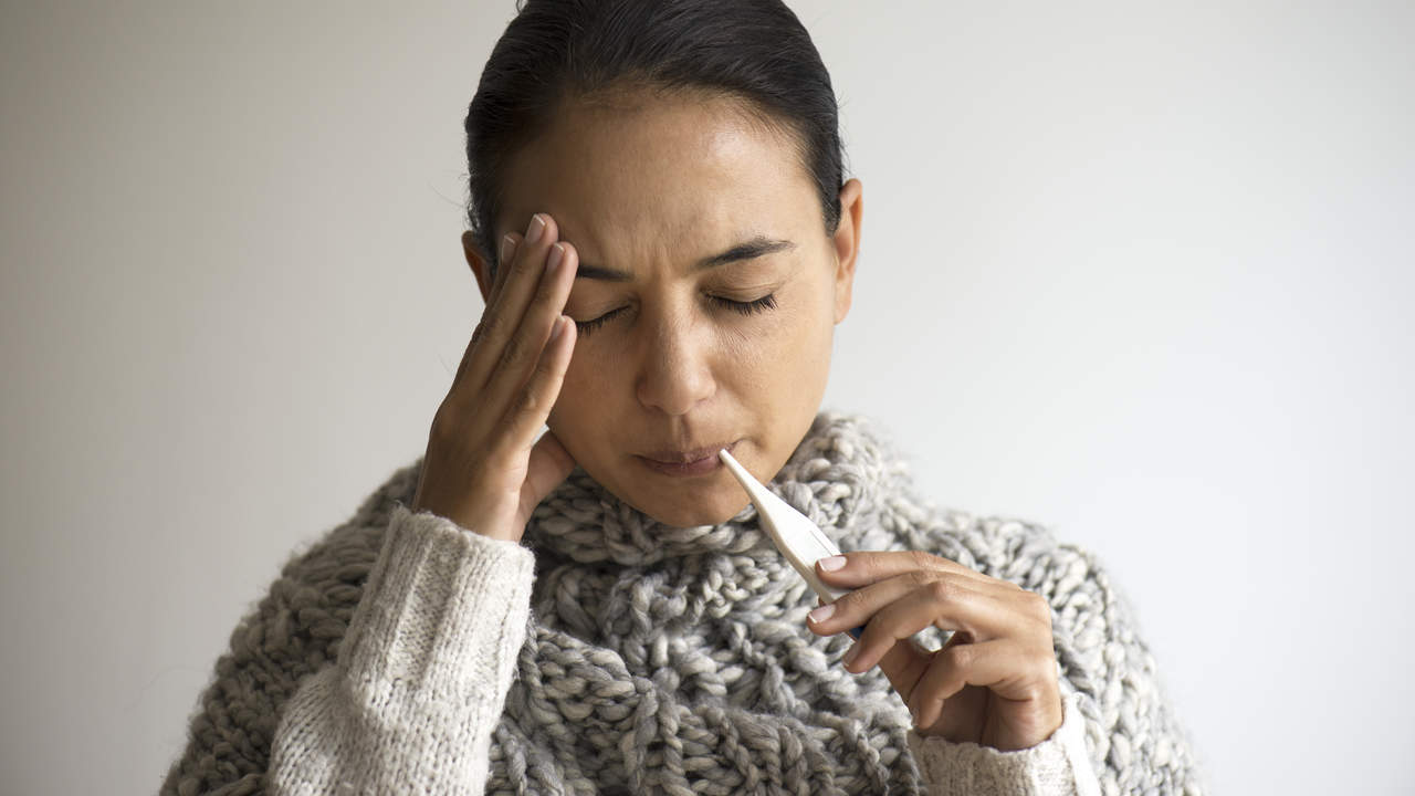 Woman with fever taking temperature with thermometer