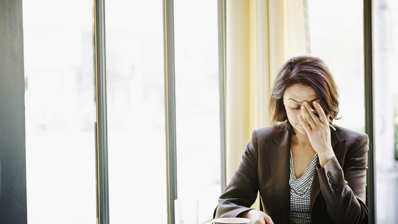 Stressed, sad, unhappy woman at her desk