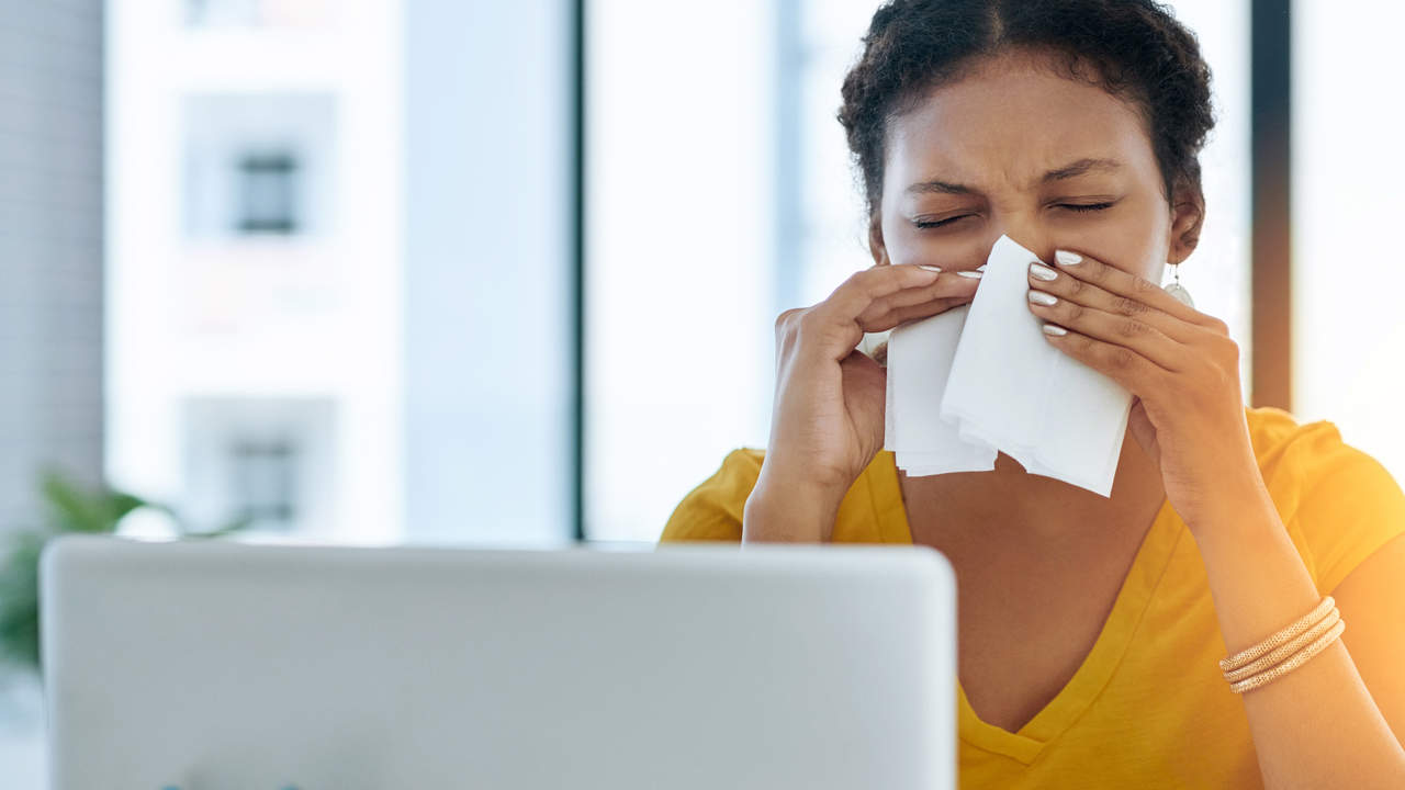 Woman blowing nose from allergies