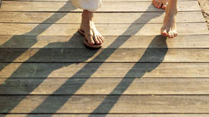 2 pairs of feet walking on a beach boardwalk