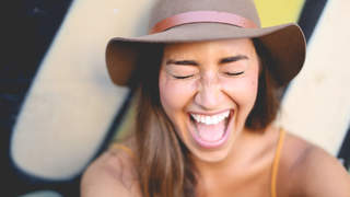 Woman with big smile and hat