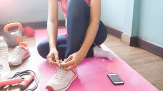 Low Section Of Woman Tying Shoelace While Sitting On Exercise Mat At Home