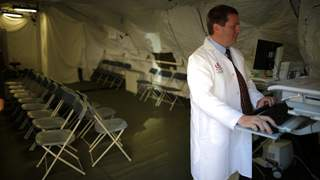 Dr Adrian Cotton stands inside a triage surge tent at Loma Linda University Health Center for patients infected with an influenza A strain known as H3N2, in Loma Linda