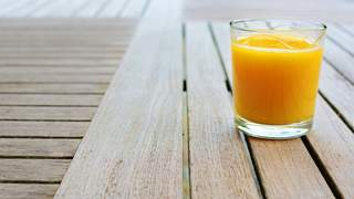 Glass of orange juice standing on wood table