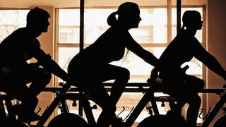 Silhouette of three people working out on exercise bikes in a gym