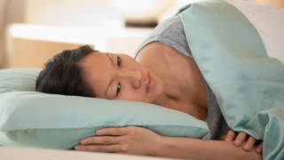 Woman lying in bed sleep disorder anxiety tracker orthsomnia
