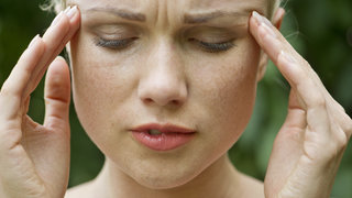 woman-rubbing-temples-headache-migraine