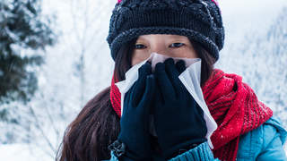 Woman blowing nose in cold weather and snow