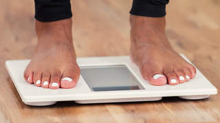 Woman standing on bathroom scale weight loss
